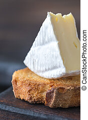 Toast with Camembert cheese on the wooden board