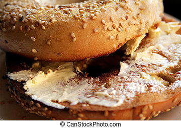 Toasted sesame seed bagel with butter on white plate