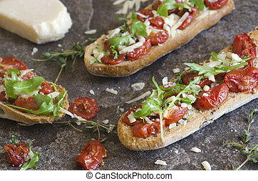 Toasted bruschettas with roasted cherry tomatoes, rocket and Parmesan