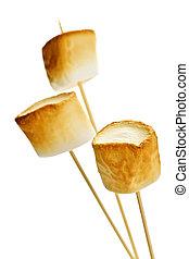 Three golden toasted marshmallows on wooden skewers