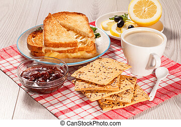 Toasted slices of bread with cheese, cookies, jam and cup of coffee.