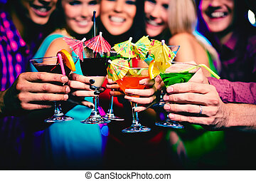 Toasting - Glasses with cocktails held by happy friends at...