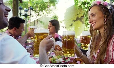 Cheerful group of friends toasting in Bavarian beer garden