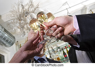 toasting on new years eve - several hands toasting with...