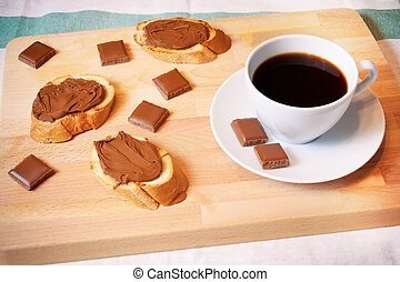 Toasts with chocolate spread and cup of coffee. Morning breakfast concept.