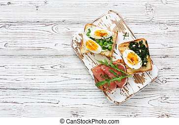 Toasts with eggs, ham and vegetables served on a white wood cutting board