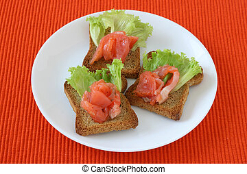 toasts with salmon on a plate