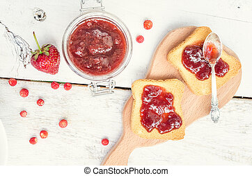 Toasts with strawberry jam for breakfast on white rusric...