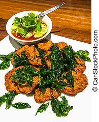 Tod Mun Pla Krai, Thai Deep Fried curried clown knifefish cake with crispy crunchy fried holy basil leaves and sweet cucumber and coriander dipping sauce, isolated on the table. Thai Authentic Recipe.