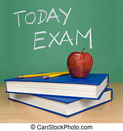 Today exam written on a chalkboard. Books, pencils and an...