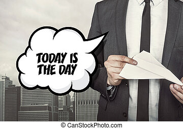 Today is the day text on speech bubble with businessman holding paper plane in hand