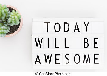 'Today will be awesome' words on a lightbox over white background, overhead view.
