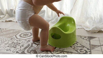 Toddler and pot at home - Baby and chamber-pot. Toddler play...