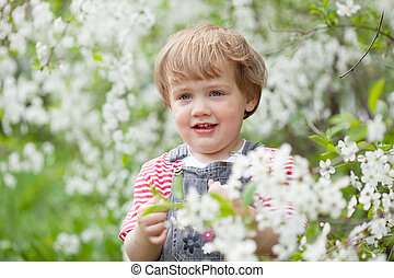 Toddler at blossoming garden