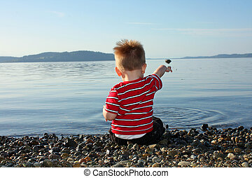 Toddler at the Beach - Toddler boy sitting on a pebbly beach...