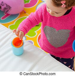 Toddler baby girl plays with colored cups