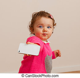 Toddler baby girl plays with smart phone.