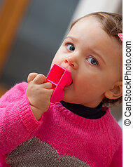 Toddler baby girl puts in her mouth rubber building blocks.