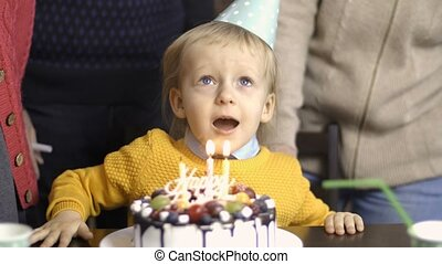Toddler boy blows candles on his birthday at home