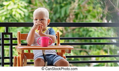 Toddler boy chews bun sitting at the highchair on the...