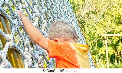 Toddler boy climbs on a climbing net