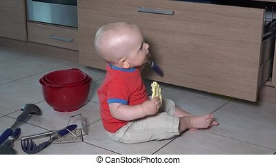 Toddler boy eat food sitting in mess on kitchen floor. ...