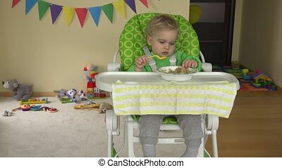 toddler boy eat mash with spoon sitting in baby high feeding...