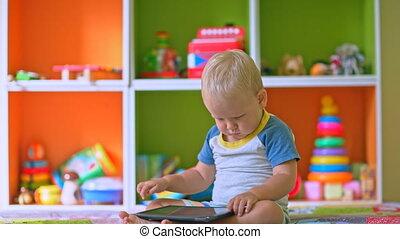 Toddler boy laughs playing tablet