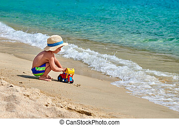 Toddler boy on beach with toys