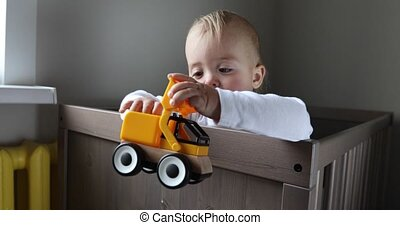 Toddler boy playing with colorful toy tractor - Closeup of...