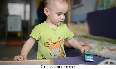 Toddler Boy playing with toy car.