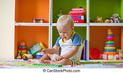 Toddler boy plays metallophone