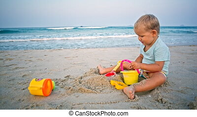 toddler boy plays sand toys beach