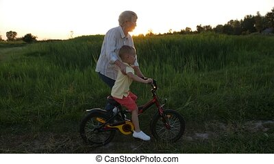 Toddler boy riding bicycle with grandmother's help
