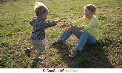 Toddler boy running to beloved grandmother in park
