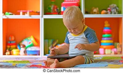 Toddler boy smiles playing with tab