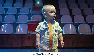 Toddler boy standing in the middle of the scene and is floodlit. Cute child examines club and lighting