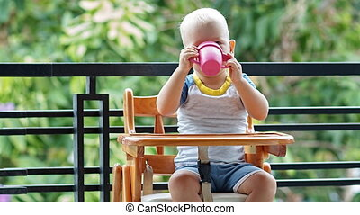 Toddler boy thirsty eagerly drinks a cup of yogurt sitting...