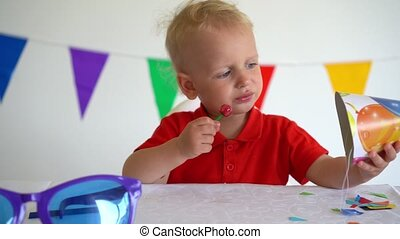 Toddler boy with candy on stick. Birthday party afterparty. Gimbal motion