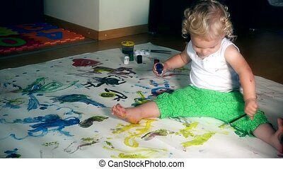 toddler boy with paintbrush and paints on floor