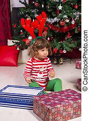Toddler boy with reindeer ears looking away