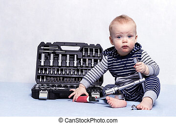 Toddler boy with tool box and adjustable wrench in his hands. Horizontal studio shot