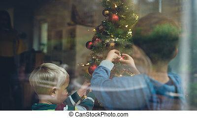 Toddler boys decorating Christmas tree