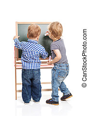 Toddler boys drawing on chalkboard over white