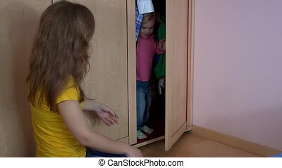 Toddler child girl get out from closet and hug mother woman....
