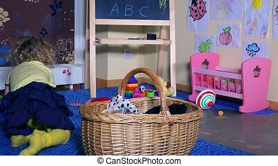 toddler child girl put toys to wicker basket. Messy room at...
