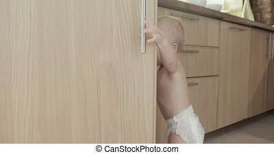 Toddler child in kitchen opens cabinet - Toddler child in...