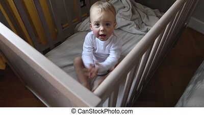 Toddler claps his hands clapping in baby crib - Adorable...