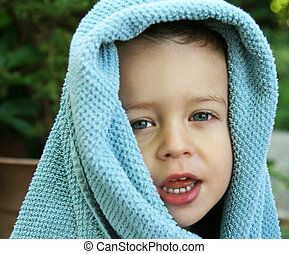 Toddler covered in a blue towel