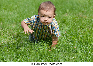 Toddler crawling in the grass